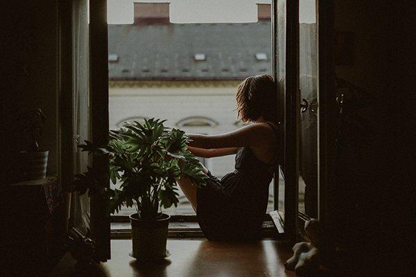 despair woman looking out window