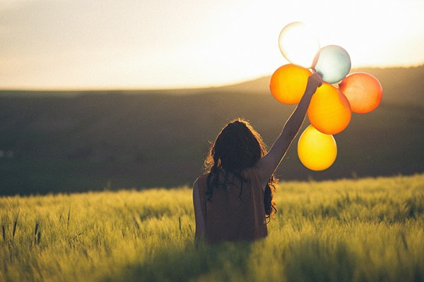 virtue happiness | woman holding balloons