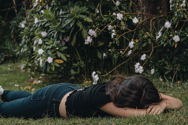 self-improvement self-attack | disappointed woman lying on grass