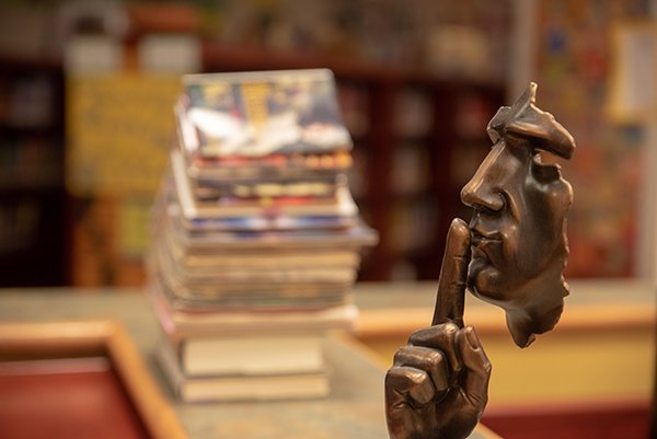 statue shushing at library | keep vices private