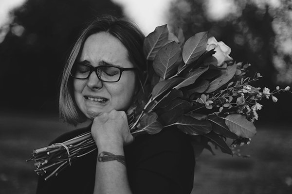 process pain | woman crying holding flowers