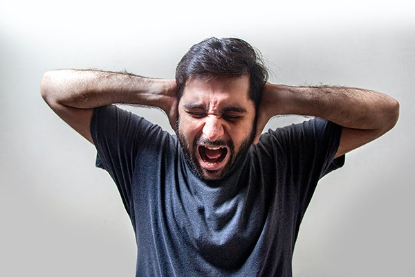 fear pain anxiety | man yelling with hands over ears