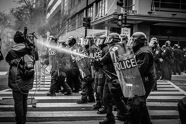 riot | police officers spraying protestors