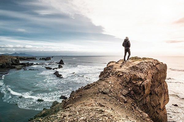 strong individual standing on cliffside overlooking ocean